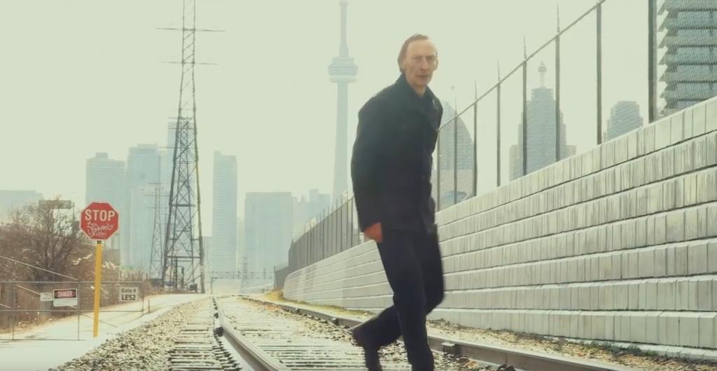 Image tirée de My One Demand, monmtrant l'un des personnages, un homme, sur une voie ferrée, avec la ville en arrière-plan.